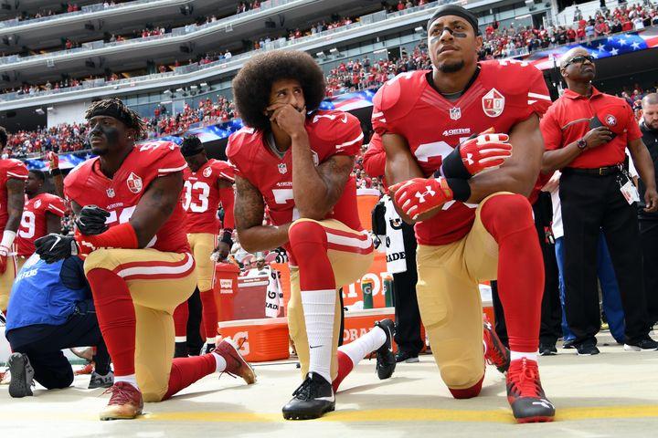 Harold (à gauche), Kaepernick (au centre) et Reid, genou à terre pendant l'Hymne nationale. (THEARON W. HENDERSON / GETTY IMAGES NORTH AMERICA)
