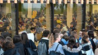 Des lycéens manifestent contre les épreuves communes de contrôle continu du baccalauréat tandis que d'autres attendent de passer leur examen, le 20 janvier 2020 au lycée René Cassin de Montfort-sur-Meu, en Ile-et-Vilaine (DAMIEN MEYER / AFP)