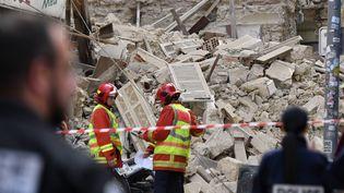 Des pompiers et des policiers recherchent des victimes, sur le site où deux immeubles se sont effondrés, le 5 novembre 2018 à Marseille (Bouches-du-Rhône). (GERARD JULIEN/AFP)