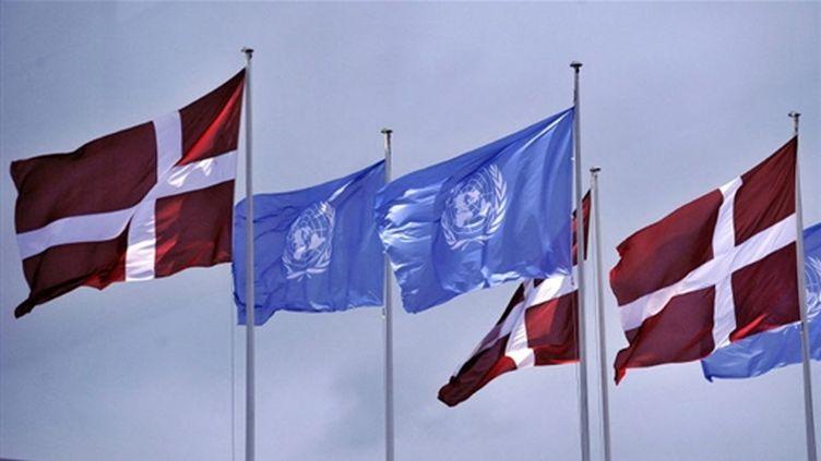 Drapeaux danois et ceux de l'ONU flottent au-dessus du Bella Center de Copenhague où a lieu la conférence (AFP PHOTO / ATTILA KISBENEDEK)