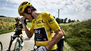 Le Britannique Geraint Thomas se rince les yeux après avoir reçu du gaz lacrymogène,le 24 juillet 2018, pendant la 16e étape du Tour de France. (MARCO BERTORELLO / AFP)