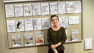 """La dessinatrice de """"Charlie Hebdo"""" Coco prend la pose devant ses créations, lors d'une exposition au musée Wilhelm-Busch de la caricature et du dessin, le 18 octobre 2016 à Hanovre (Allemagne). (HOLGER HOLLEMANN / DPA / AFP)"""