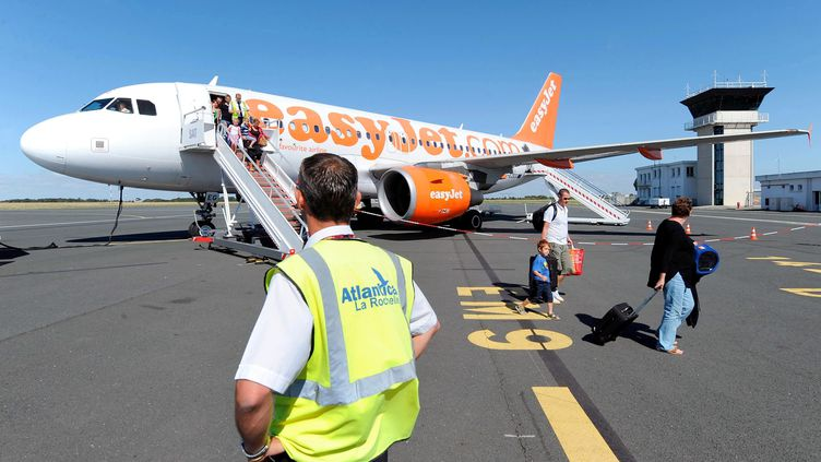 Des passagers descendent d'un avion de la compagnie EasyJet, le 25 juillet 2009, à La Rochelle (Charente-Maritime). (REMY GABALDA / AFP)