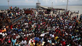 La population sinistrée de la ville de Jérémie en Haïtiattend le déchargement de l'aide d'un navire néerlandais, le 16 octobre 2016, après le passage de l'ouragan Matthew. La catastrophe a fait plus de 540 morts.  (CARLOS GARCIA RAWLINS / REUTERS)