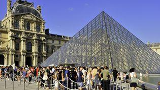 Des visiteurs font la queue devant la Pyramide du Louvre, le 11 décembre 2019. (TRIPELON-JARRY / AFP)