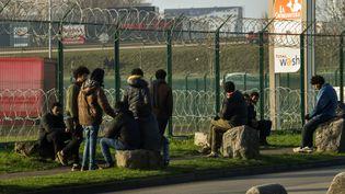 Des migrants attendent près d'un parking du terminal d'embarquement pour l'Angleterre, à Calais (Pas-de-Calais), le 12 janvier 2018. (PHILIPPE HUGUEN / AFP)
