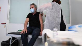 Un médecin du travail vaccine un salarié avec une dose d'AstraZeneca le 25 février 2021 à Paris, dans un centre réservé aux salariés du secteur de la communication. (ALAIN JOCARD / AFP)