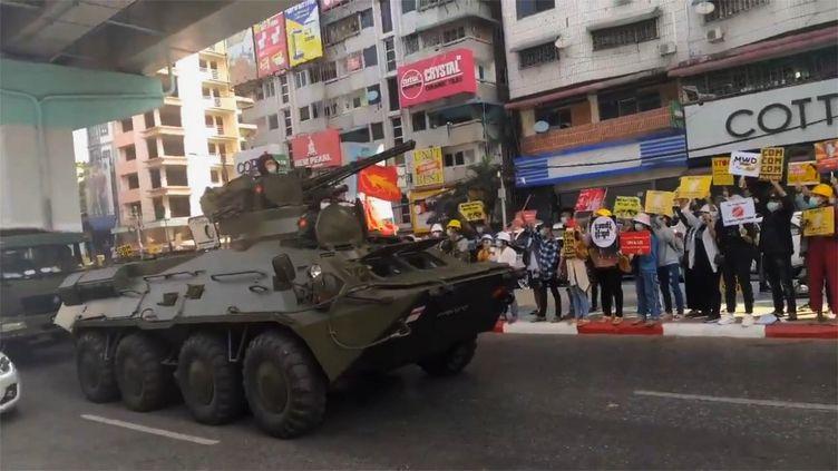 Des manifestants tenant des pancartes s'alignent sur le bord de la route alors que des chars et des camions de l'armée se dirigent vers le centre-ville de Rangoun, le 15 février 2021. (EYEPRESS NEWS / AFP)