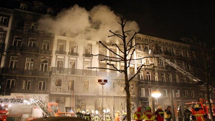 Les pompiers luttent contre le feu après l'explosion qui a secoué deux immeubles du centre de Liège (26/01/10) (AFP / Michel Krakowski)