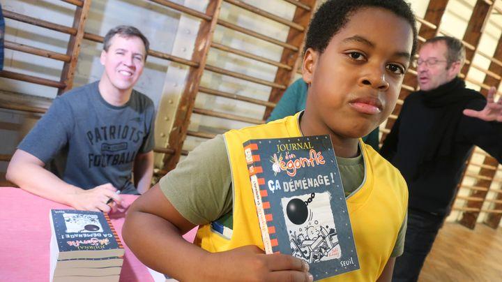 """Roy, 11 ans, en 6e au collège Georges Rouault pose avec """"Le journal d'un dégonflé"""" (Seuil Jeunesse) et l'auteur Jeff Kinney (en arrière plan), le 10 décembre 2019 (Laurence Houot / franceinfo Culture)"""