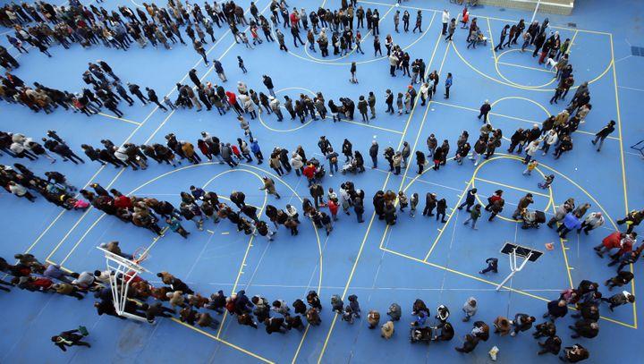 Des Barcelonais font la queue dans un gymnase pour participer à la consultation sur l'avenir de la Catalogne. (ALBERT GEA / REUTERS)