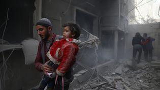 Un homme porte un enfant après un bombardement dans la ville de Douma, en Syrie, le 7 février 2018. (BASSAM KHABIEH / REUTERS)