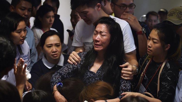 Des familles des passagers du vol QZ8501 d'AirAsia en pleurs à l'aéroport de Surabaya (Indonésie), le 30 décembre 2014. (MANAN VATSYAYANA / AFP)