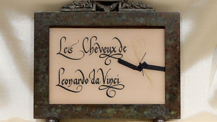 Une mèche de cheveux attribuée à Léonard de Vinci enchâssée dans un cadre. (VINCENZO PINTO / AFP)