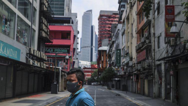 Un homme marche dans une rue vide, à Kuala Lumpur (Malaisie), le 2 avril 2020. (FAZRY ISMAIL / EPA)