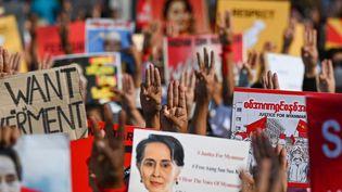 Des manifestants brandissent des pancartes en soutien àl'ex-dirigeante birmane Aung San Suu Kyi, écartée du pouvoir par un coup d'Etat de la junte militaire, le 16 février 2021 à Rangoun. (YE AUNG THU / AFP)