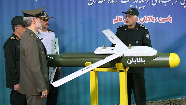 """Le ministre de la Défense iranien Amir Hatami (à gauche, devant) près du missile """"Balaban"""" lors d'une cérémonie de présentation de trois nouveaux missiles iraniens à Téhéran, le 6 août 2019. (IRANIAN DEFENCE MINISTRY / AFP)"""