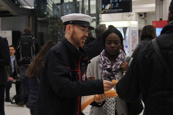 Benoît, agent de départ en grève, distribue des tracts aux voyageurs de la gare du Nord, à Paris, mercredi 11 avril 2018. (MAHAUT LANDAZ / FRANCEINFO)