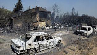 Carcasses de voitures devant une maison ravagée par un incendie de forêt à Orgon (Bouches-du-Rhône), le 26 août 2012. (FRANCK PENNANT / AFP)