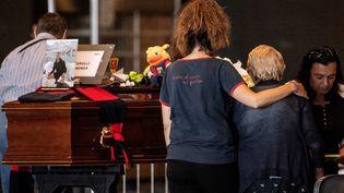 Des familles se recueillent sur les cercueils de leurs proches qui ont perdu la vie dans l'effondrement du pont à Gênes, le 17 août 2018. (MARCO BERTORELLO / AFP)