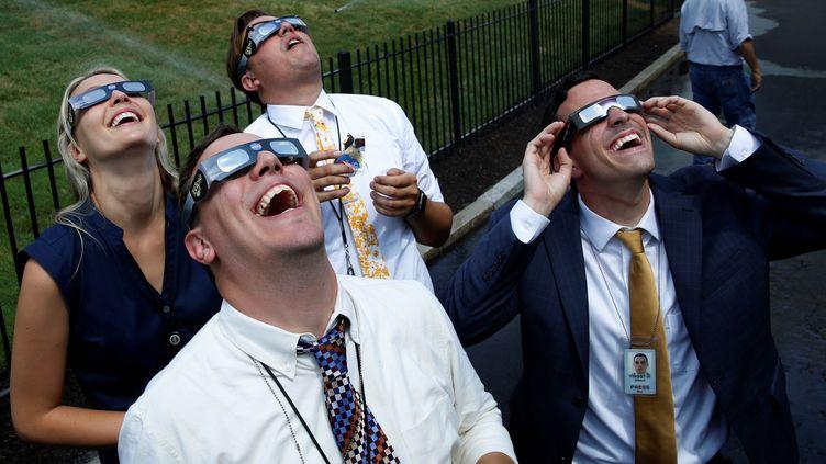 Des journalistes accrédités à la Maison Blanche observent l'éclipse à la résidence présidentielle américaine, le 21 août 2017 à Washington. (YURI GRIPAS / REUTERS)