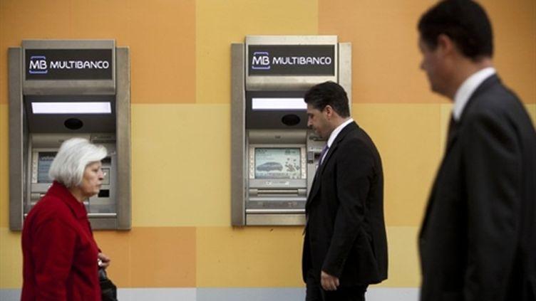 Des habitants de Lisbonne devant des distributeurs, le 7 avril 2011. (AFP PHOTO/PATRICIA DE MELO MOREIRA)