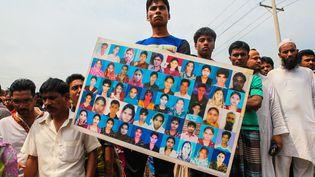 Un proche d'une victime du Rana Plaza, près de Dacca, au Bangladesh, porte un panneau montrant les photos d'ouvriers du textile tués dans l'effondrement du bâtiments, en 2013, vendredi 24 avril 2015. (ANIK RAHMAN / NURPHOTO / AFP)