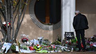 Un homme regarde les fleurs déposées devant le collège où enseignait Samuel Paty,le 19 octobre 2020, àConflans-Sainte-Honorine (Yvelines). (ANNE-CHRISTINE POUJOULAT / AFP)