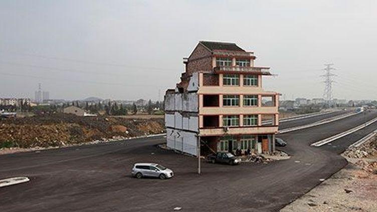 Une « maison clou» dans le milieu d'une route nouvellement construite dans la province de Zhejiang, le 24 novembre 2012. (REUTERS / Aly Song)