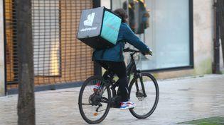 Un livreur Deliveroo dans une rue d'Amiens(Somme). Photo d'illustration. (FRED HASLIN / MAXPPP)