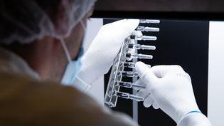 Un technicien inspecte des seringues dans un laboratoire de Sanofi à Val-de-Reuil, le 10 juillet 2020 (photo d'illustration). (JOEL SAGET / AFP)
