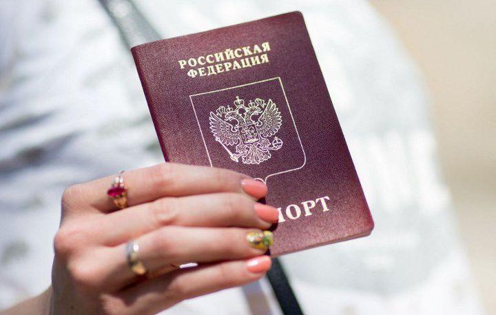 Une habitante de Narva brandit son passeport russe (juin 2016). (Kay Neitfeld / AFP)