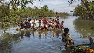 Des Rohingyas arrivent au Bangladeshen traversant la rivière Naf sur un radeau de fortune, le 11 novembre 2017. (ARNAUD FINISTRE / HANS LUCAS / AFP)