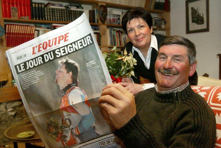 Les parents d'Antoine Dénériaz avec le journal L'Equipe le 13 février 2006. (JEAN-PIERRE CLATOT / AFP)