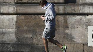 Un joggeur, visage masqué dans le centre de Paris le 8 avril 2020. (ALAIN JOCARD / AFP)