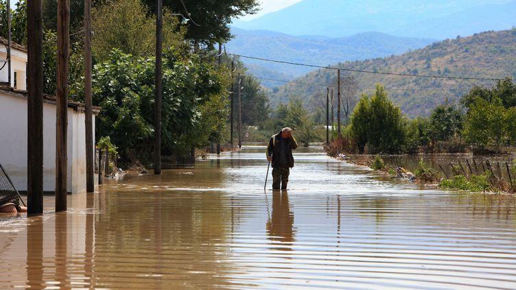 Un homme marche dans une rue inondée du village de Magoula, dans le centre de la Grèce, le 19 septembre 2020. (KOSTAS MANTZIARIS / AFP)