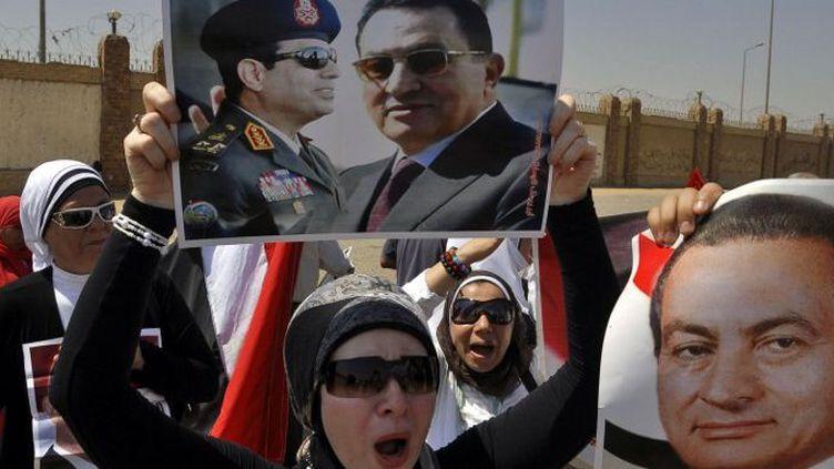 Une partisane de l'ancien président égyptien Hosni Moubarak porte un portrait de lui et du général Abdel Fattah al-Sissi, devant l'Académie de police avant le procès de l'ancien président, le 25 août 2013 au Caire. (Engy Imad / AFP)