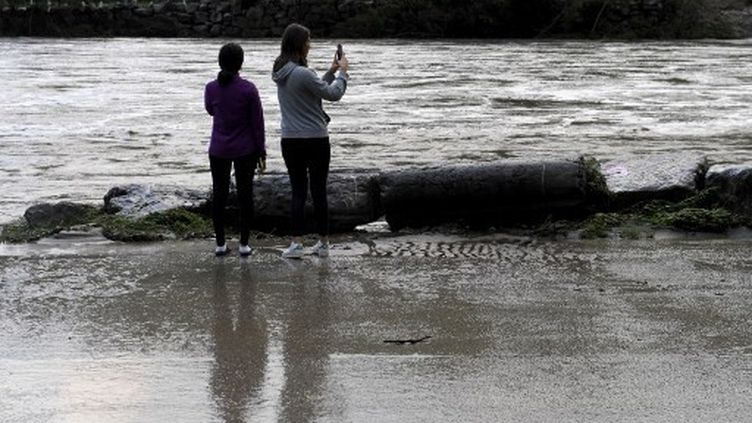 Des habitants filment leGardon après les inondations à Anduze, dans le sud-est de la France, le 19 septembre 2020. (NICOLAS TUCAT / AFP)
