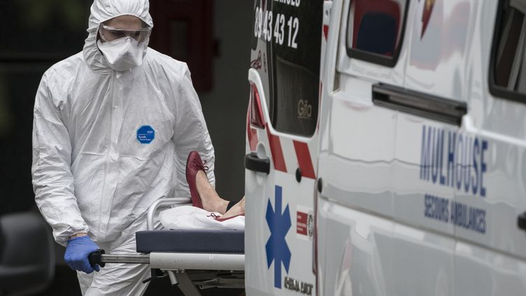 Un soignant rentre un brancard dans une ambulance, le 22 mars 2020, devant l'hôpital de Mulhouse (Haut-Rhin). (SEBASTIEN BOZON / AFP)
