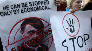 Des manifestants ukrainiens à Kiev (Ukraine), le 11 mars 2014. Leurs affiches comparent Vladimir Poutine à Adolf Hitler. (ANATOLII STEPANOV / AFP)