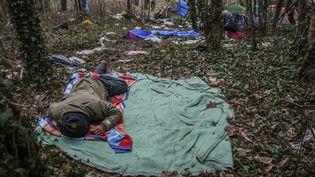Atmosphère dans un camp improvisé de migrants dans la forêt de Calais, où certains dorment dehors sur de simples duvets au milieu des déchets. (MAXPPP)