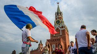 Des supporters français agitent un drapeau, samedi 14 juillet à Moscou (Russie), à la veille de la finale de la Coupe du monde. (MLADEN ANTONOV / AFP)