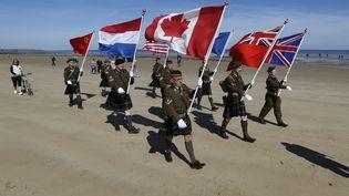 Des amateurs d'histoire venus des Pays-Bas marchent sur Juno Beach, zone d'atterrissage des soldats canadiens pour le D-Day, en Normandie, le 6 juin 2014. (CHRIS HELGREN / REUTERS)