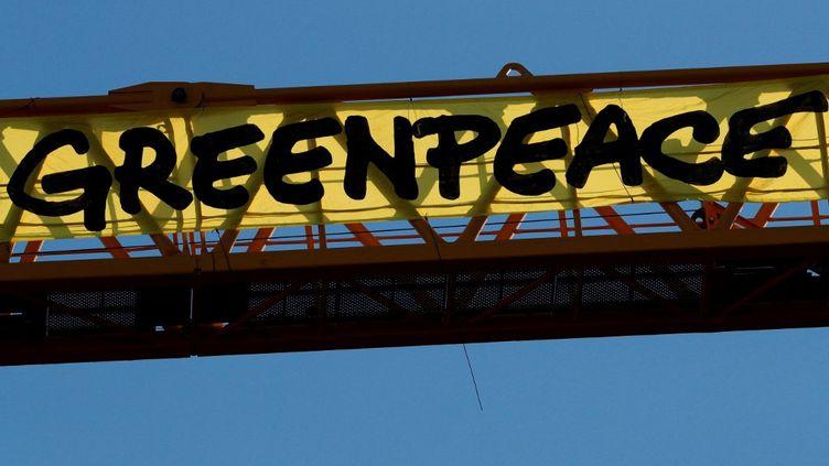 """Une banderole géanteportant l'inscription """"Greenpeace"""" lors d'une manifestation contre la politique du gouvernement français en matière d'environnement, sur le chantier de la cathédrale Notre-Dame, à Paris, le 9 juillet 2020. (GEOFFROY VAN DER HASSELT / AFP)"""