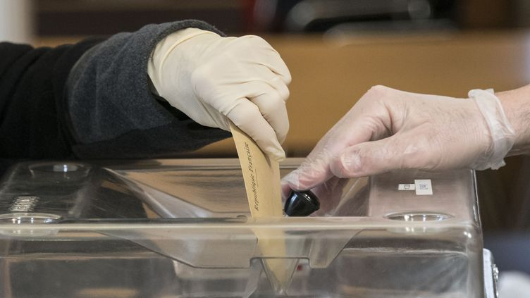 A voter wearing plastic gloves casts a ballot on March 15, 2020, in Kingersheim, eastern France, during the first round of mayoral elections in France, as France battles the coronavirus that causes the COVID-19 disease. - Officials have been told to disinfect voting booths and ballot boxes throughout the day, and sinks and hand gels will be made available. People will be urged to get in and out quickly to avoid lines, and floor markings will be laid out to ensure they stay one metre (3.3 feet) from one another. Authorities have already eased proxy voting rules for people at risk or infected with coronavirus and ordered to confine themselves to their homes, as well as for people in retirement homes. People can also come with their own pens for marking ballots. (Photo by SEBASTIEN BOZON / AFP) (SEBASTIEN BOZON / AFP)