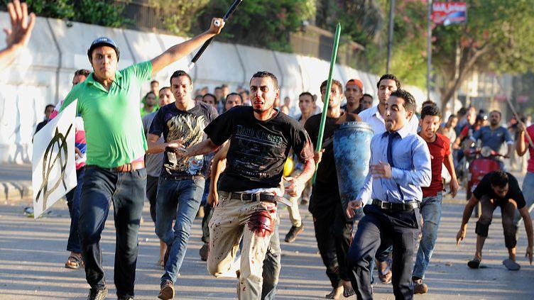Partisans et adversaires du président égyptien déchu Mohamed Morsi s'affrontent aux abords de la place Tahrir au Caire (Egypte), le 22 juillet 2013. (FAYEZ NURELDINE / AFP)