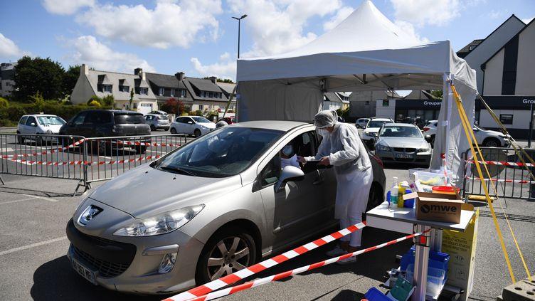 Un biologiste procède à un dépistage de Covid-19 sur un parking de Plabennec (Finistère), le 20 juillet 2020. (FRED TANNEAU / AFP)