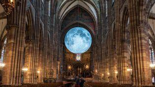 """L'oeuvre """"Museum of the Moon"""", de Luke Jerram, installée dans la nef de la cathédrale Notre-Dame de Strasbourg, dans le cadre de la manifestion """"L'industrie magnifique"""", du 3 au 13 juin 2021 (PATRICK HERTZOG / AFP)"""