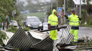 Des hommes nettoyent les rues après le passage du cyclone Bejisa, vendredi 3 janvier 2014, à Saint-Pierre (La Réunion). (RICHARD BOUHET / AFP)