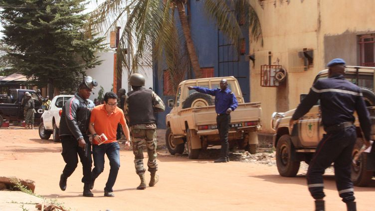 Un soldat aide un otage qui quitte la scène devant l'hôtel Radisson Blu à Bamako (Mali), le 20 novembre 2015. (HAROUNA TRAORE / AP / SIPA)